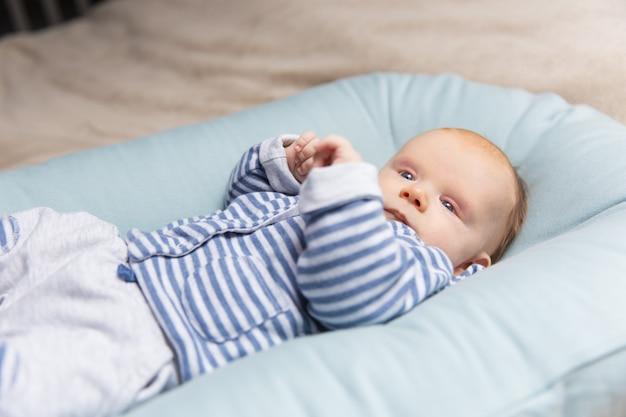 Nieuwsgierige peinzende roodharige baby in blauwe en grijze kleding Gratis Foto