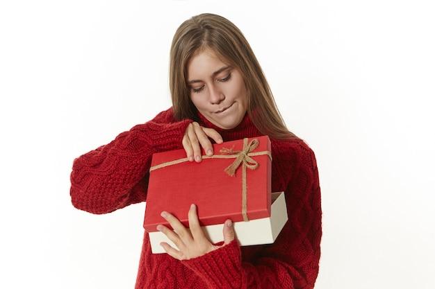 Nieuwsgierige vrouw in gebreide warme trui met mooie geschenkdoos, die ongeduldig opent en met belangstelling naar binnen kijkt. Gratis Foto