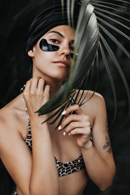 Nieuwsgierige vrouw met ooglapjes camera kijken. buiten schot van stijlvolle vrouw in tulband poseren op exotische achtergrond. Gratis Foto