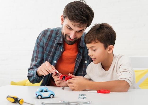 Nieuwsgierige zoon en vader die speelgoedauto's bevestigen Gratis Foto