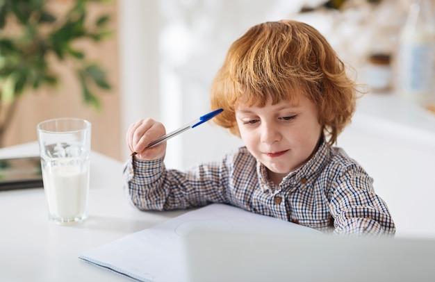 Nieuwsgierigheid is de sleutel. heerlijk bewonderenswaardig slim kind dat aan de tafel in de keuken zit en notities opschrijft terwijl hij een glas melk drinkt Premium Foto