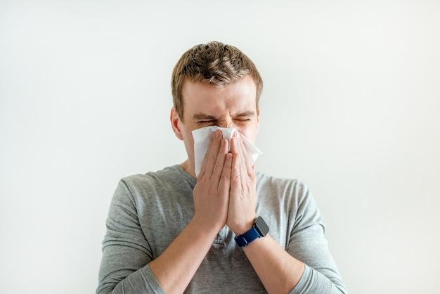Niezen man in zakdoek blazen afvegen lopende neus, symptomen ademhalingsinfectie, coronavirus en griepsymptomen Premium Foto