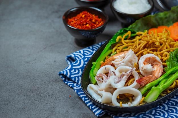Noedels gegarneerd met zeevruchten noodles, krokante noedels, thais eten Gratis Foto