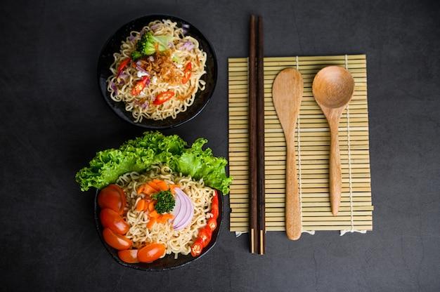 Noedels kruidig in de kom met ingrediënten en eetstokjes, houten lepel op zwarte cementoppervlakte Gratis Foto
