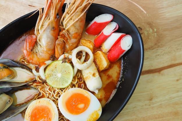 Noedels kruidige garnalensoep in zwarte kom op houten tafel, tom yum goong Premium Foto