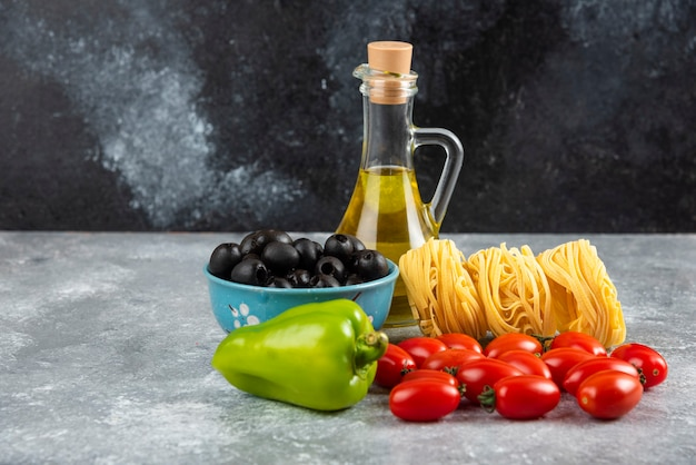 Noedels, olie en diverse groenten op stenen tafel. Gratis Foto