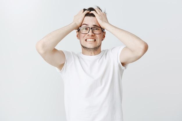 Noodlijdende man in paniek grijpt het hoofd en kijkt angstig Gratis Foto