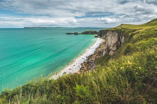 Noord-ierland kustlijn. heldere zee, groen land. Premium Foto
