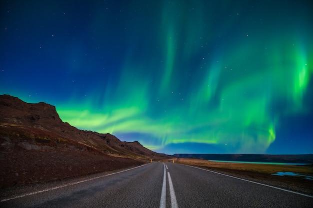 Noordelijk licht boven lege weg en berg in de herfst, ijsland Premium Foto