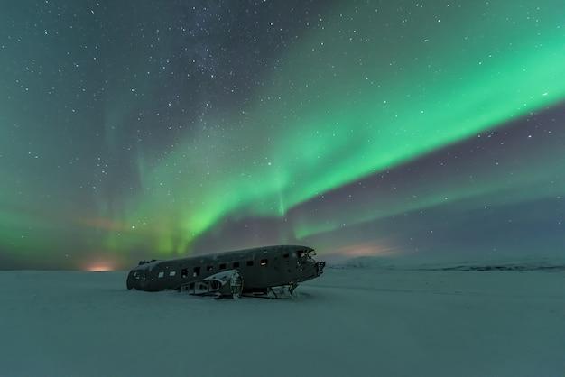 Noordelijke lichten over vliegtuigschipbreuk in ijsland Premium Foto