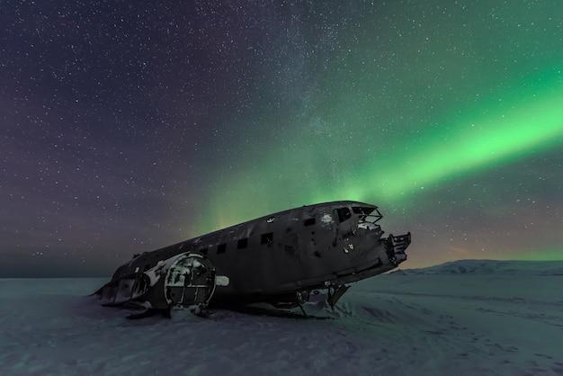Noordelijke lichtenaurora borealis over vliegtuigschipbreuk in ijsland Premium Foto