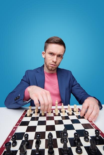 Nors jonge man die naar je kijkt terwijl hij bij het schaakbord zit en in zijn eentje in isolatie speelt Premium Foto