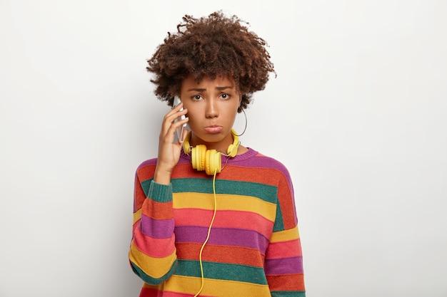 Nors ontevreden afro-amerikaanse meisje heeft onaangenaam gesprek via smartphone, draagt kleurrijke casual gestreepte trui, gebruikt gele koptelefoon, ontevreden over iets Gratis Foto
