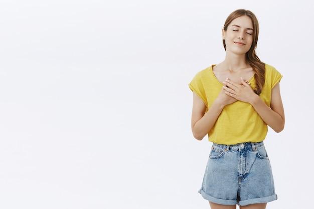 Nostalgisch gelukkig schattig meisje lachend met gesloten ogen en handen op hart Gratis Foto