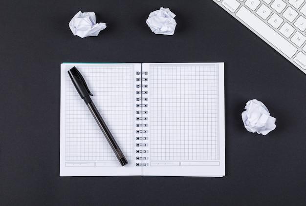 Nota die concept met notitieboekje, pen, verpletterd document, toetsenbord op zwarte hoogste mening nemen als achtergrond. horizontaal beeld Gratis Foto
