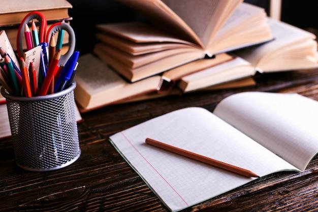 Notebook, open boeken en schoolbenodigdheden op een donkere houten tafel tegen de achtergrond van een schoolbord Premium Foto