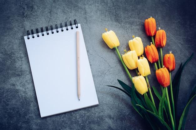 Notebook, potlood en bloem op zwart Premium Foto