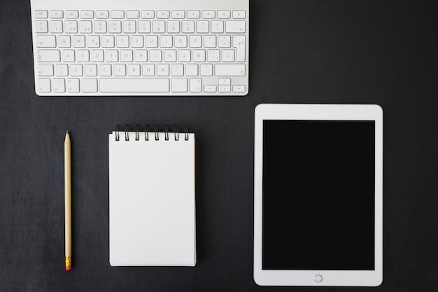 Notebook, tablet en toetsenbord op donker bureau Premium Foto