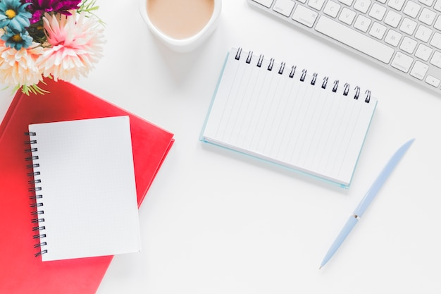Notebooks in de buurt van koffiekopje en toetsenbord op tafel Gratis Foto