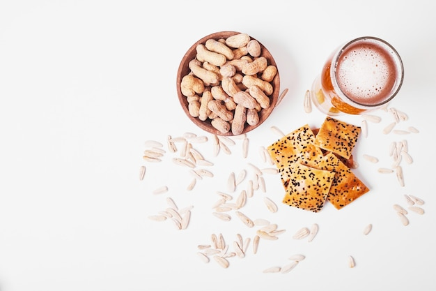 Noten en crackers met bier op wit. Gratis Foto