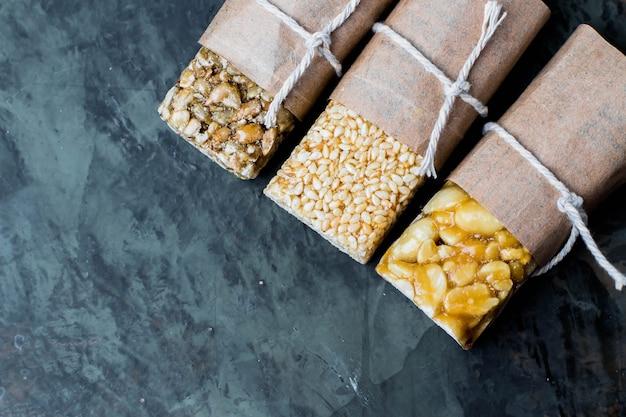Noten in karamel, honing op groene stenen tafel achtergrond Premium Foto