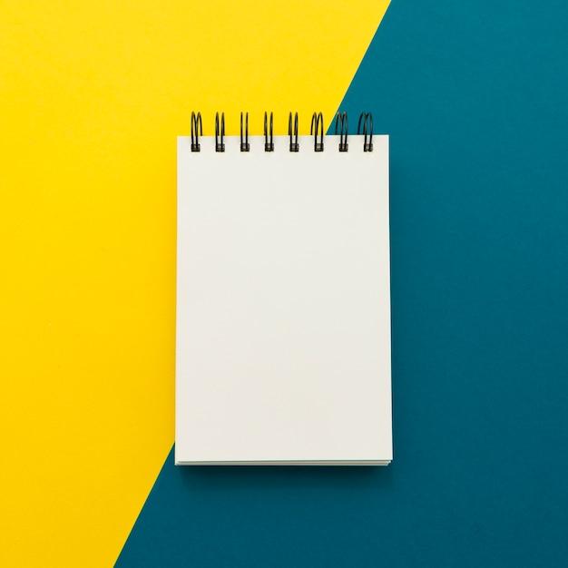 Notitieblok op gele en blauwe achtergrond Gratis Foto