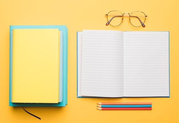 Notitieblok openen en stapel handboeken naast glazen en set potloden Gratis Foto