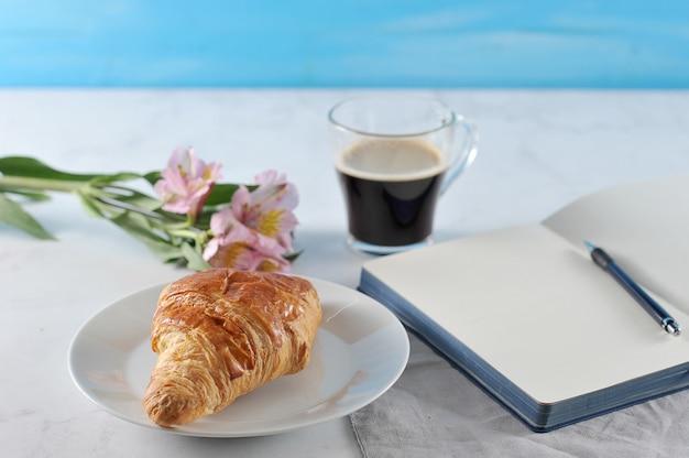 Notitieblok openen met bloemen en zwarte koffie en croissant Premium Foto