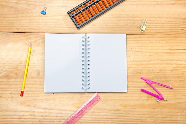 Notitieblok openen met schoolbenodigdheden en briefpapier op de houten tafel Premium Foto