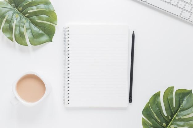 Notitieboekje dichtbij koffiekop en toetsenbord op lijst met groene bladeren Gratis Foto