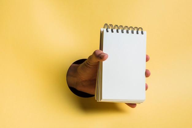 Notitieboekje door persoon met gele achtergrond wordt gehouden die Gratis Foto
