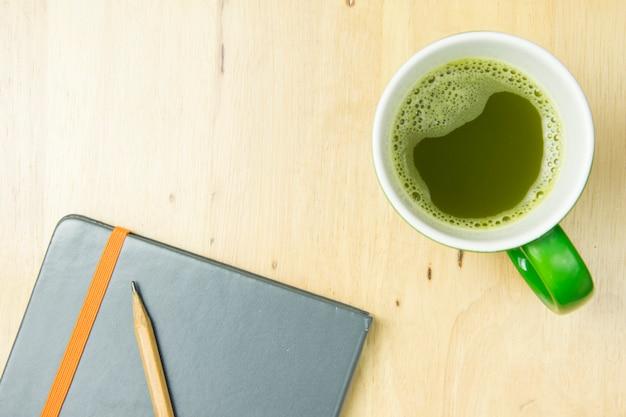 Notitieboekje en potlood met greentea op houten achtergrond. bovenaanzicht, plat leggen concept. Premium Foto