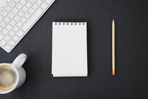 Notitieboekje en potlood met toetsenbord en koffie Gratis Foto
