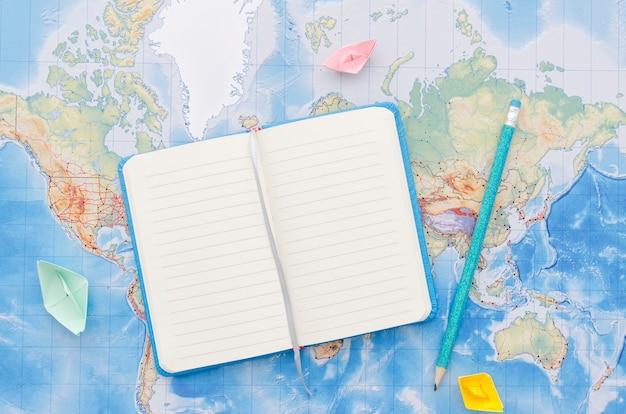 Notitieboekje en potlood op wereldkaart Gratis Foto