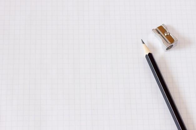Notitieboekje in een kooi met een potloodclose-up, spatie voor de ontwerper, businessplan Premium Foto
