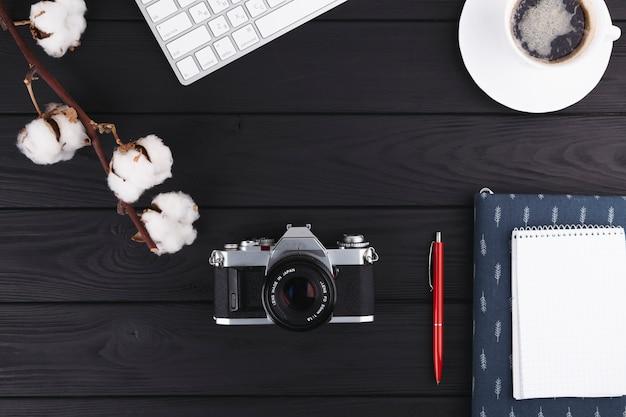 Notitieboekje met camera en koffie op lijst Gratis Foto