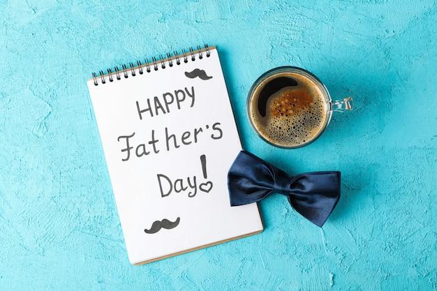 Notitieboekje met de dag van inschrijvings gelukkige vaders, blauwe vlinderdas en kop van koffie op kleurenachtergrond, ruimte voor tekst en hoogste mening Premium Foto