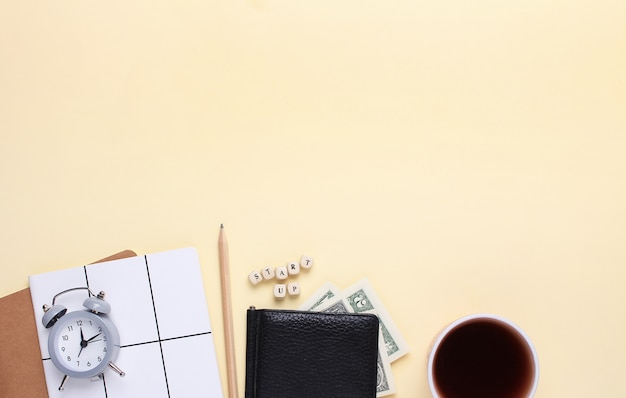 Notitieboekje met een potlood, portemonnee, wekker, kopje koffie op een beige achtergrond met het woord opstarten van houten letters. Premium Foto