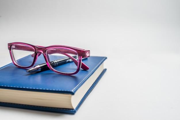 Notitieboekje met glazen en pen, boek met glazen, blauw notitieboekje met glazen, boek met kop thee Premium Foto