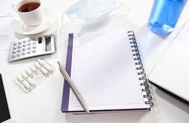 Notitieboekje met pen en beschermend masker op een witte lijst. zakelijke items en medische masker op een witte tafel. Premium Foto