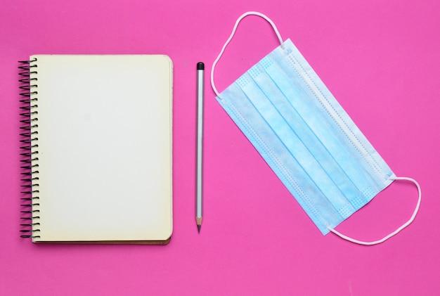 Notitieboekje met pen, gaasverband op roze achtergrond, hoogste mening Premium Foto