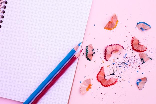 Notitieboekje met potlood en scherpte op roze achtergrond Gratis Foto