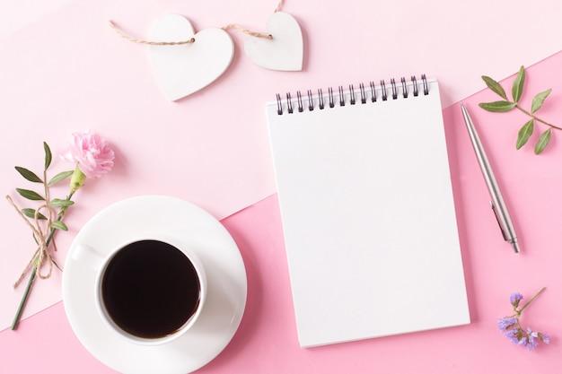 Notitieboekje met schone pagina, kopje koffie, bloem, pen en houten hart op roze achtergrond. bovenaanzicht, vlakke stijl. Premium Foto