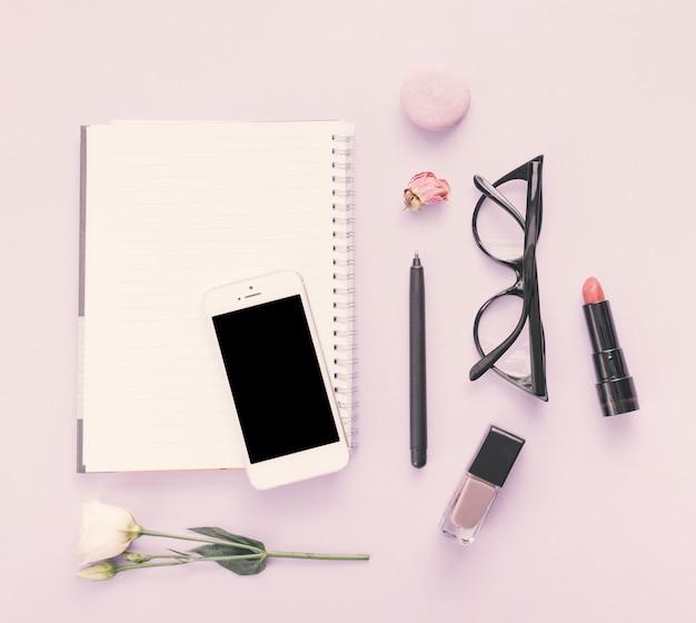 Notitieboekje met smartphone, bloem en schoonheidsmiddelen op lijst Gratis Foto