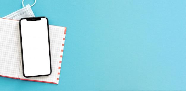 Notitieboekje met smartphone met het lege scherm en medisch gezichtsmasker op blauw achtergrond hoogste concept van het menings het verre werk Premium Foto