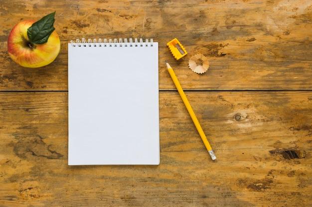 Notitieboekje met whittled het schrijven potlood en appel dichtbij Gratis Foto