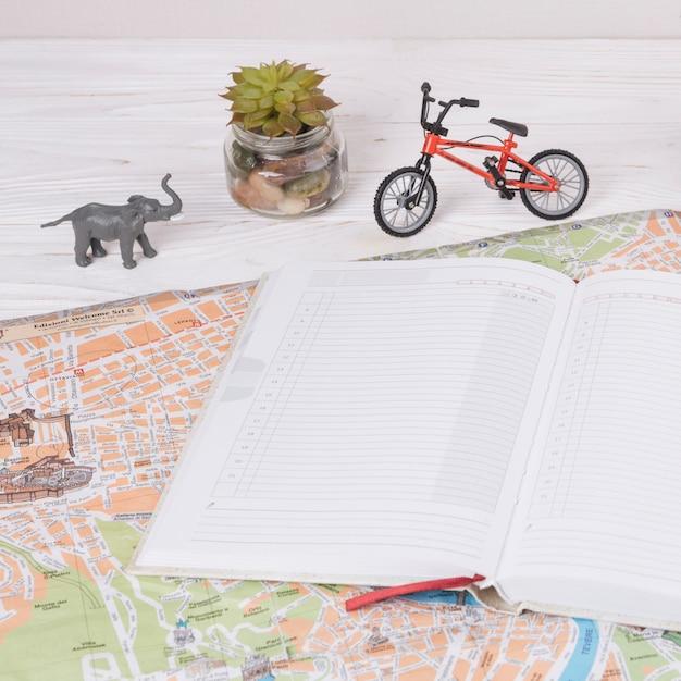 Notitieboekje op kaart dichtbij stuk speelgoed dier en fiets Gratis Foto