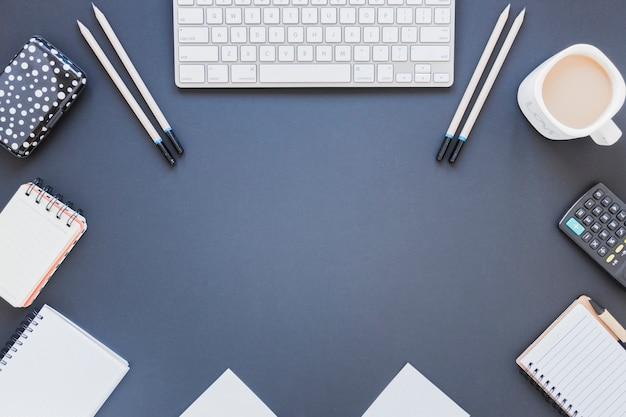 Notitieboekjes dichtbij calculator en toetsenbord op bureau met koffiekop Gratis Foto