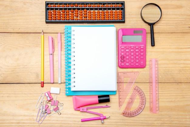 Notitieboekjes met schoolbenodigdheden en briefpapier op de houten tafel Premium Foto