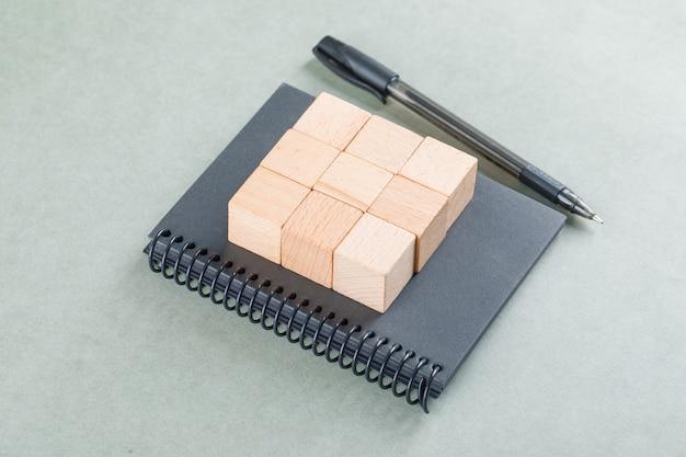 Notities bedrijfsconcept met houten blokken, pen op salie kleur tabel hoge hoek bekijken. Gratis Foto
